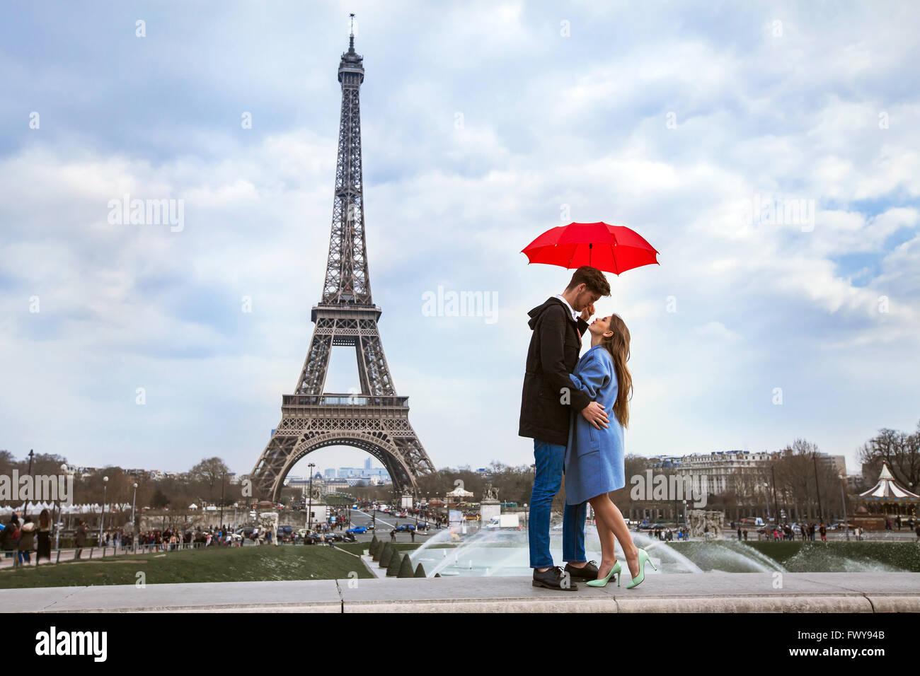 Hermosa joven con sombrilla cerca de la Torre Eiffel, luna de miel en París, momento romántico Foto de stock