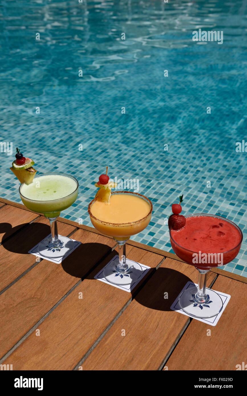 Rojo amarillo y verde cócteles en un deck de madera junto a una piscina Foto de stock