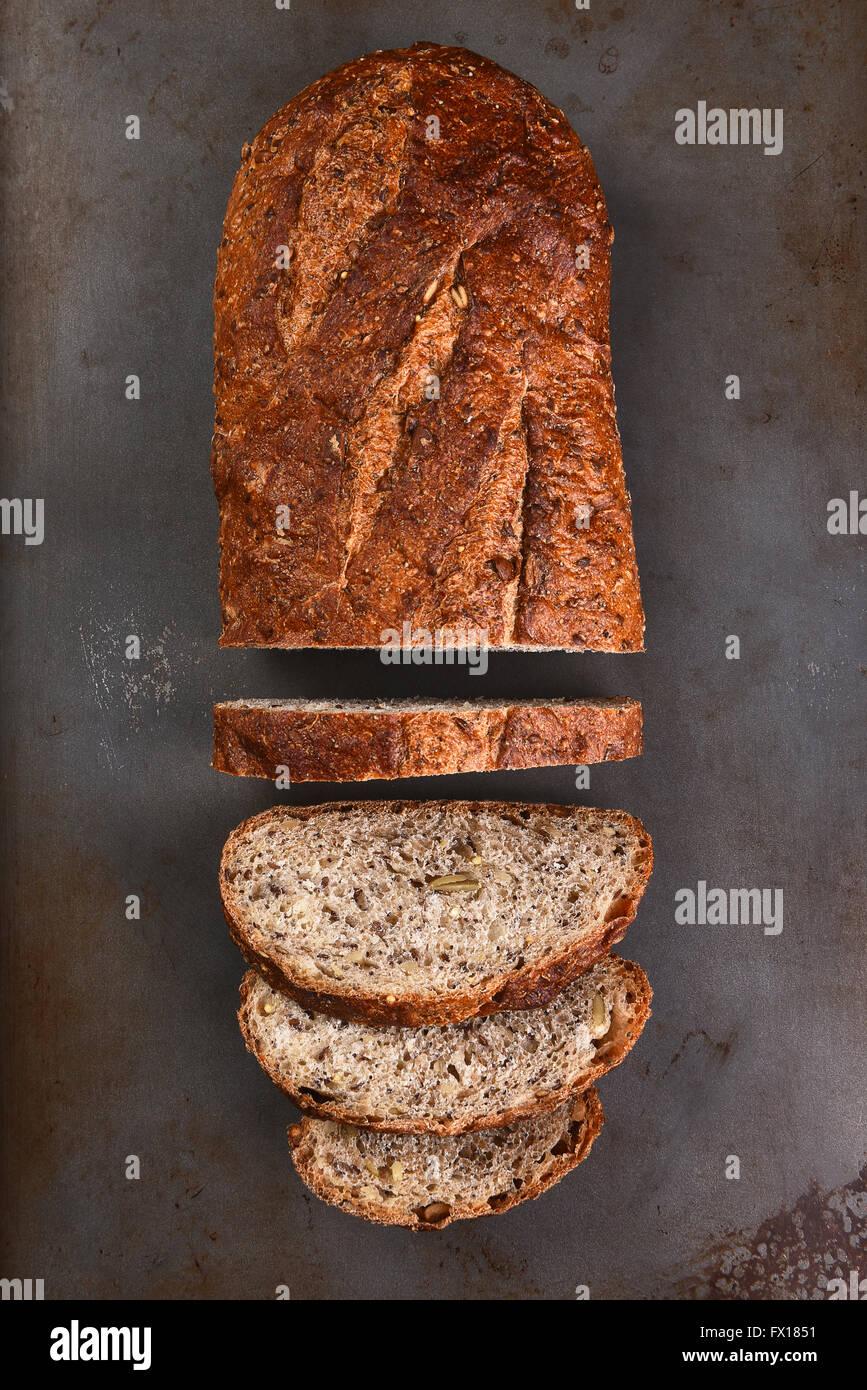 Vista superior de una hogaza de pan de grano múltiple en una bandeja para hornear. El pan está parcialmente Imagen De Stock