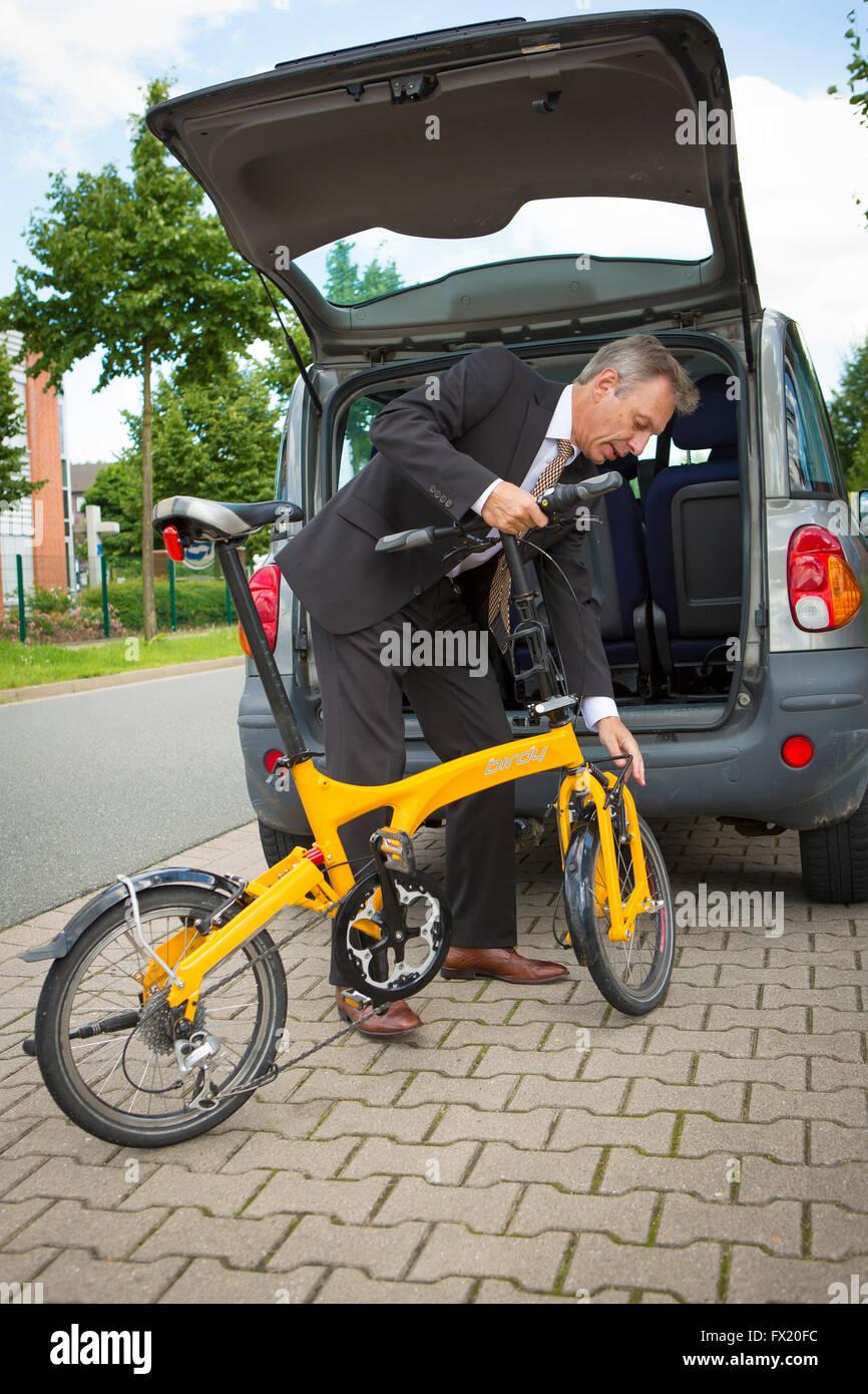 Hombre de negocios agarra su bicicleta plegable en el maletero del coche Imagen De Stock