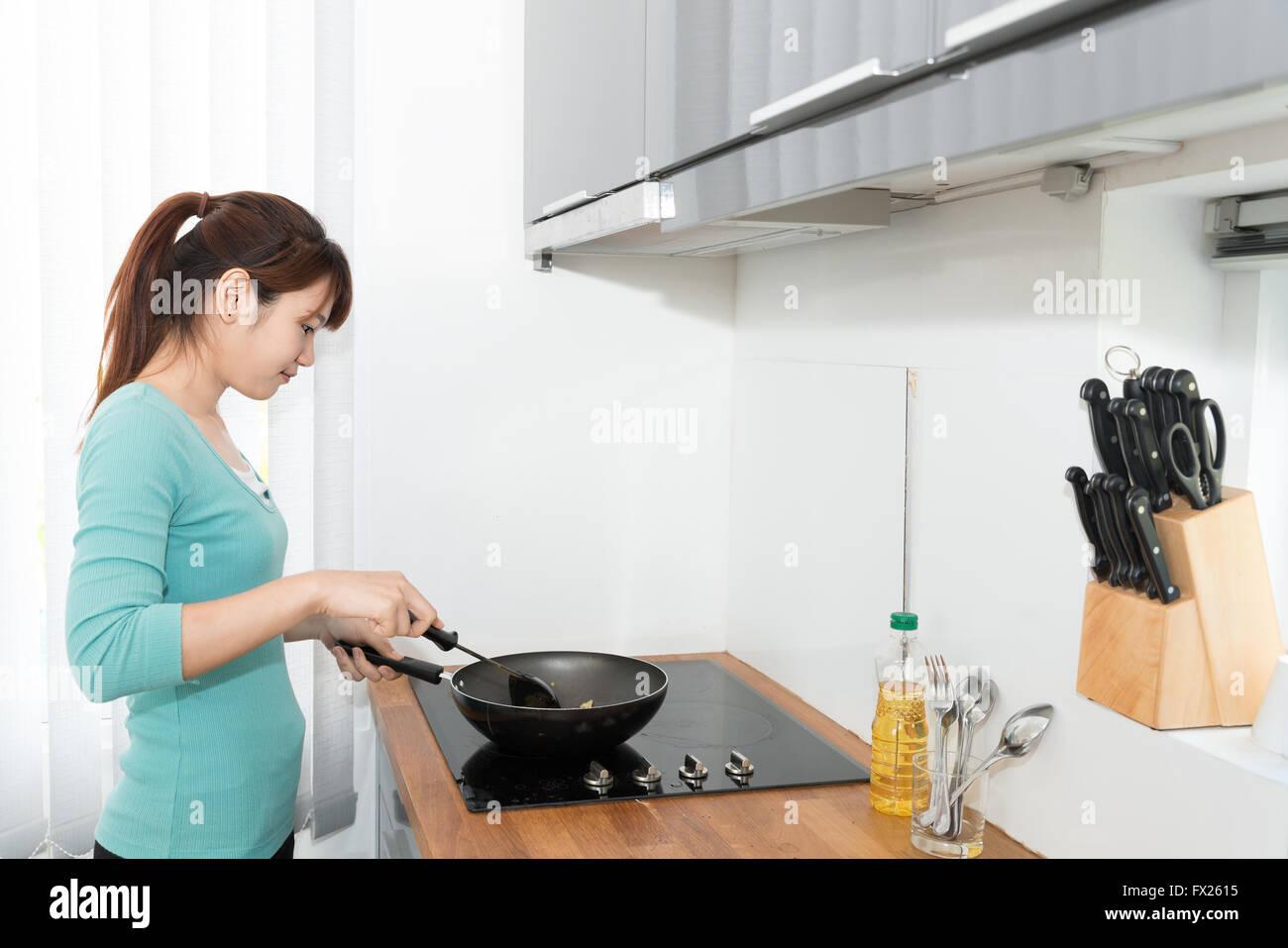Mujer joven asiática en la cocina para cocinar en casa Imagen De Stock