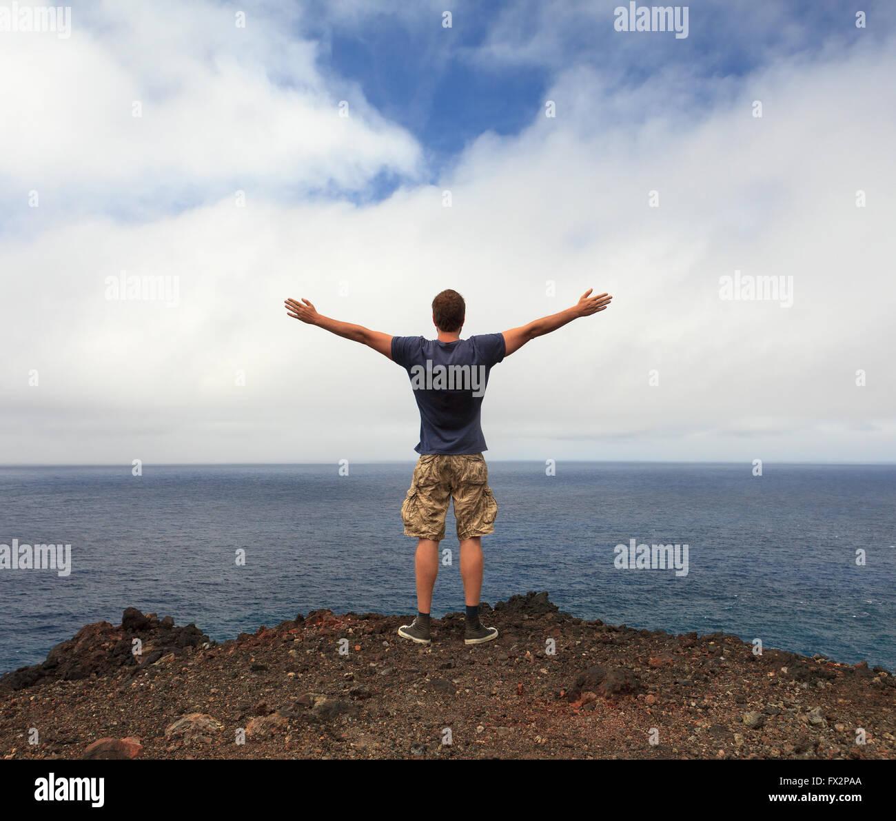 Libertad o amante de la naturaleza concepto - el hombre con los brazos levantados a orillas del mar Foto de stock