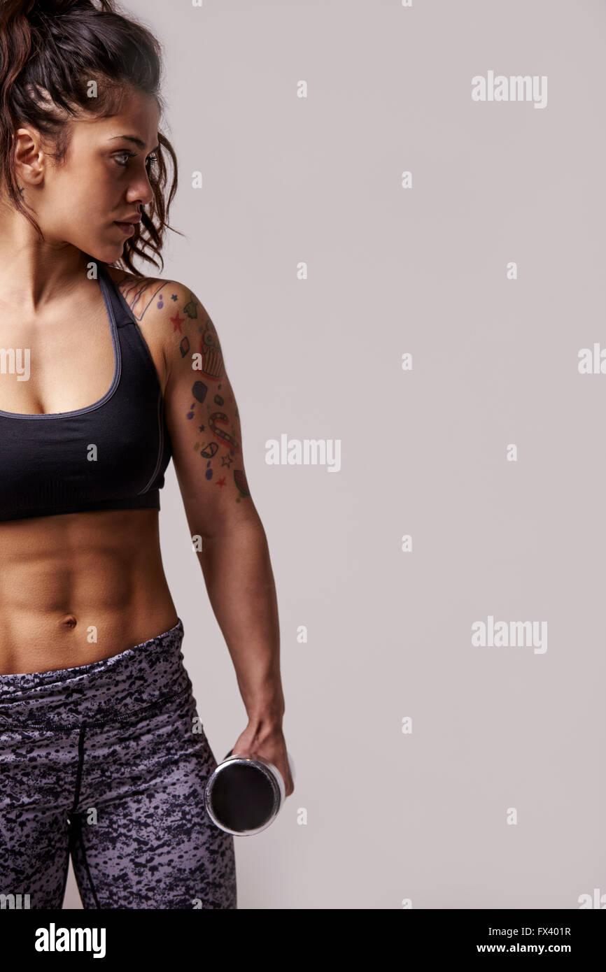 Joven morenaza muscular con pesas, vertical Imagen De Stock
