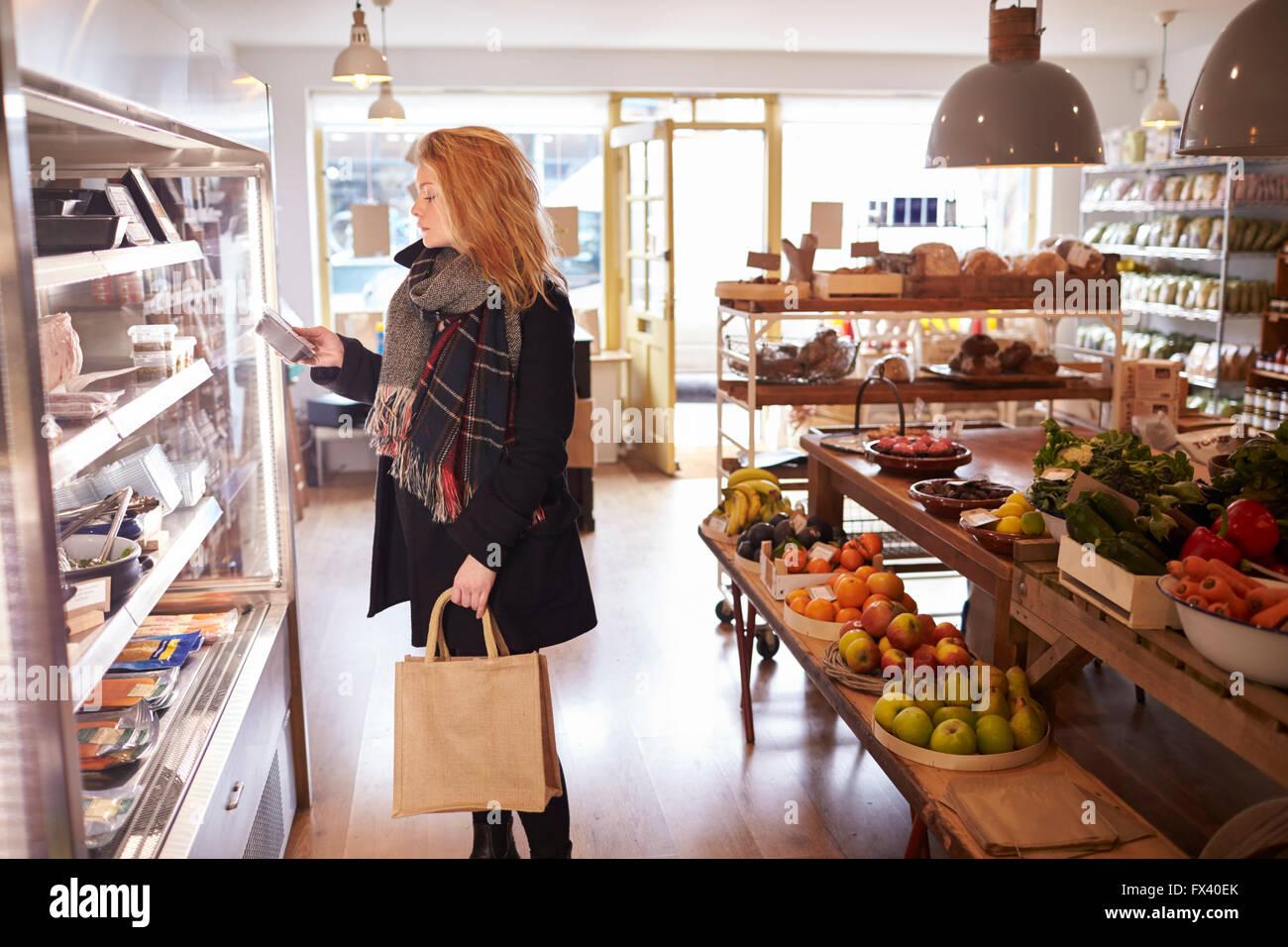 Mujer mirando en pantalla refrigerados de delicatessen Imagen De Stock