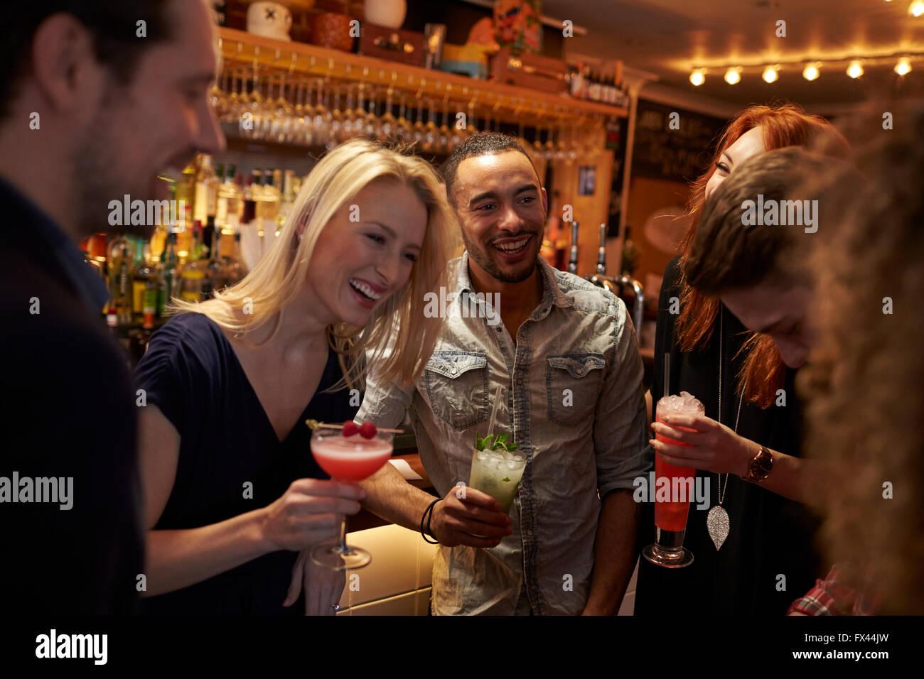 Un grupo de amigos, la reunión para tomar bebidas por la tarde en el Cocktail Bar Imagen De Stock