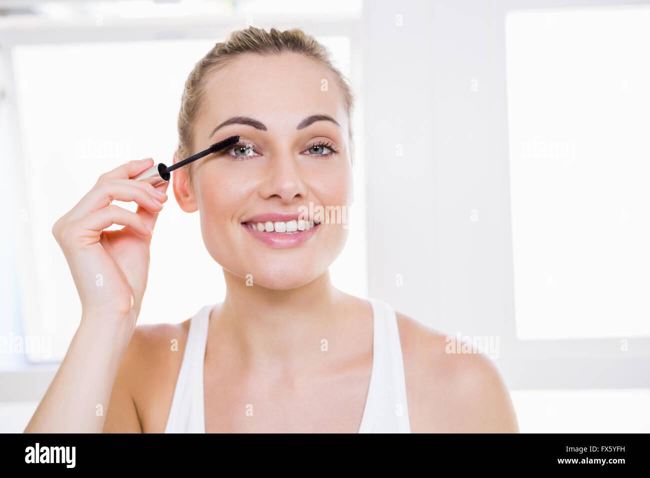 Mujer joven de aplicar el rímel en el baño. Imagen De Stock
