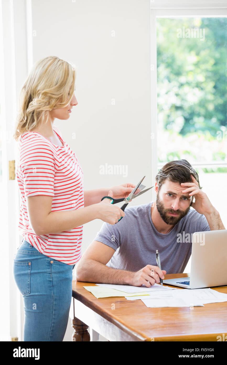 Mujer cortando una tarjeta de crédito mientras se tensa con facturas hombre sentado en la mesa Imagen De Stock