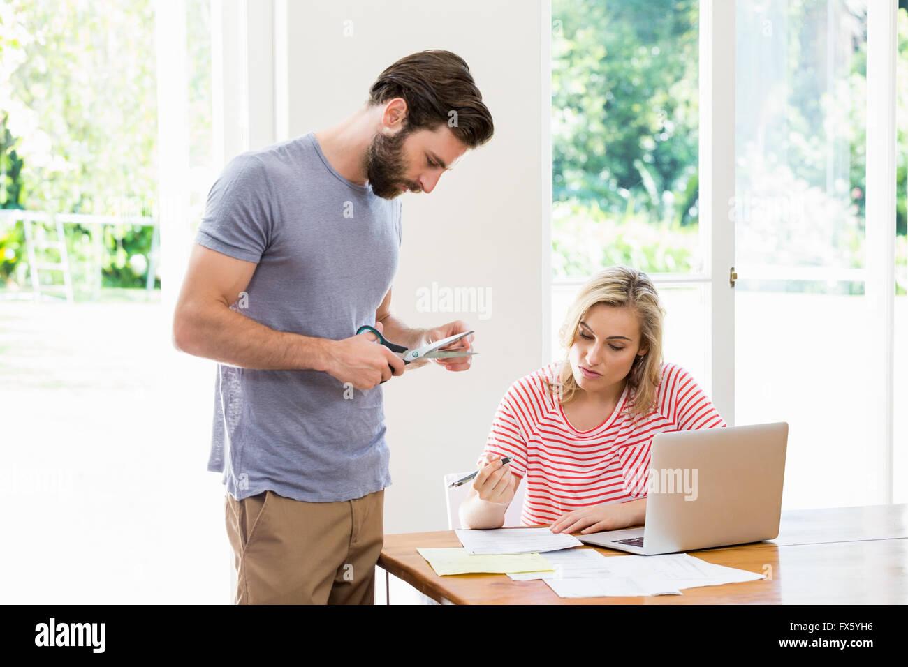 Hombre corte de una tarjeta de crédito mientras se tensa mujer sentada con facturas en la mesa Imagen De Stock