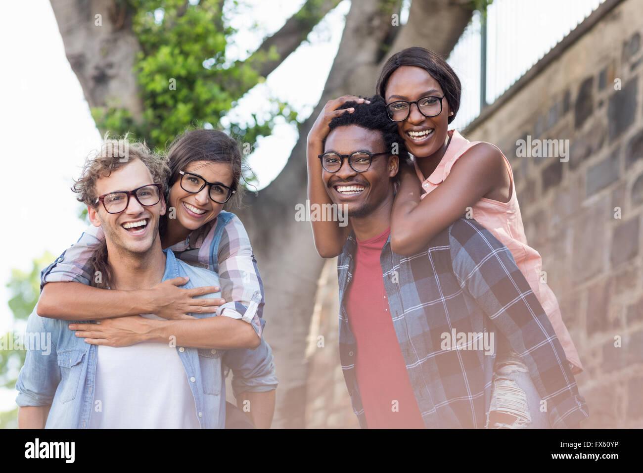 Los hombres jóvenes dando a las mujeres piggyback Imagen De Stock
