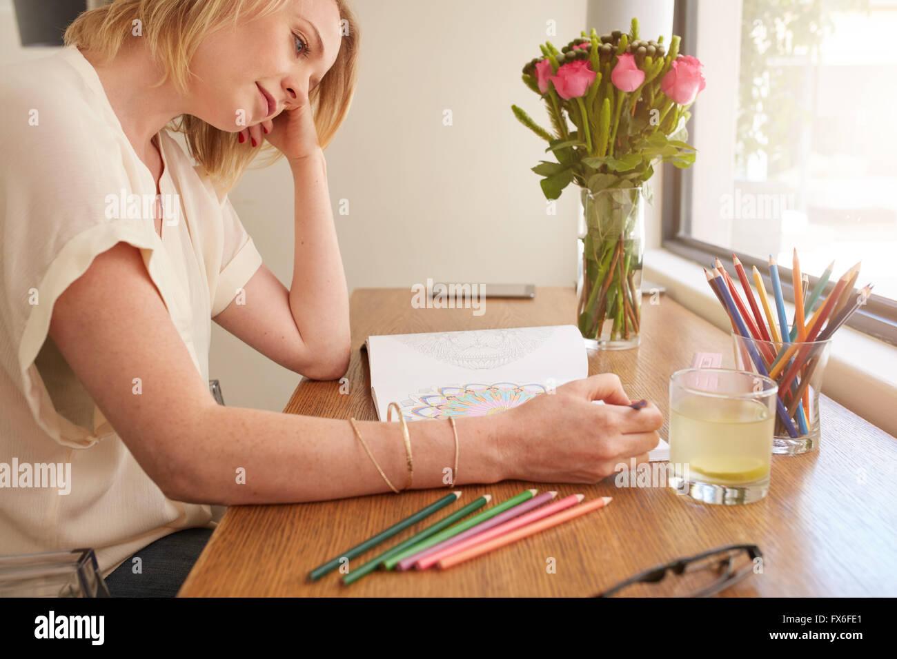 Mujer sacando un adulto coloring book mientras cómodamente sentado en una mesa junto a una ventana. Imagen De Stock
