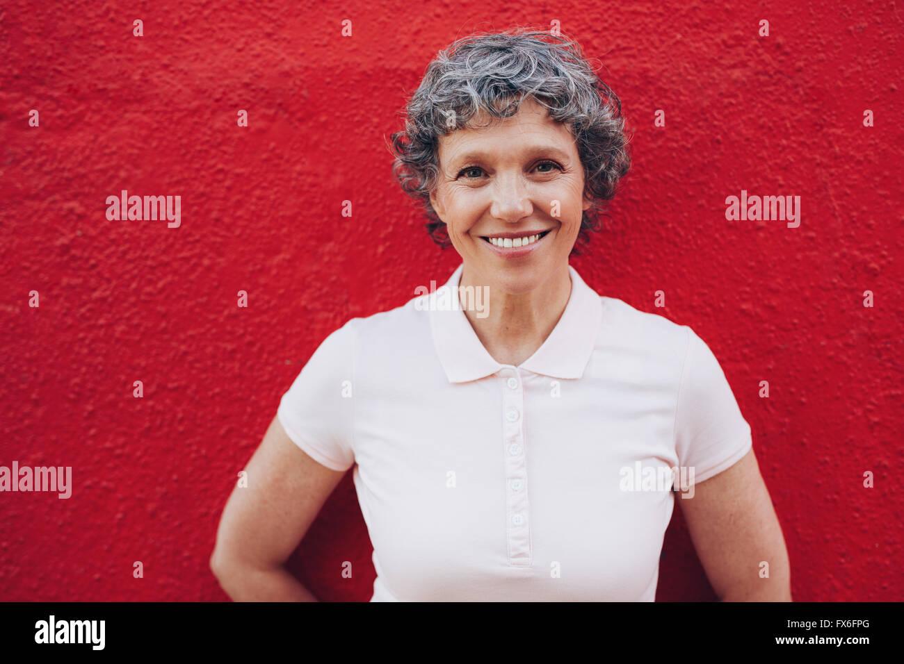 Retrato de mujer de pie senior contra el fondo rojo. Sonriendo a mediados adulto hembra rojo contra la pared. Imagen De Stock