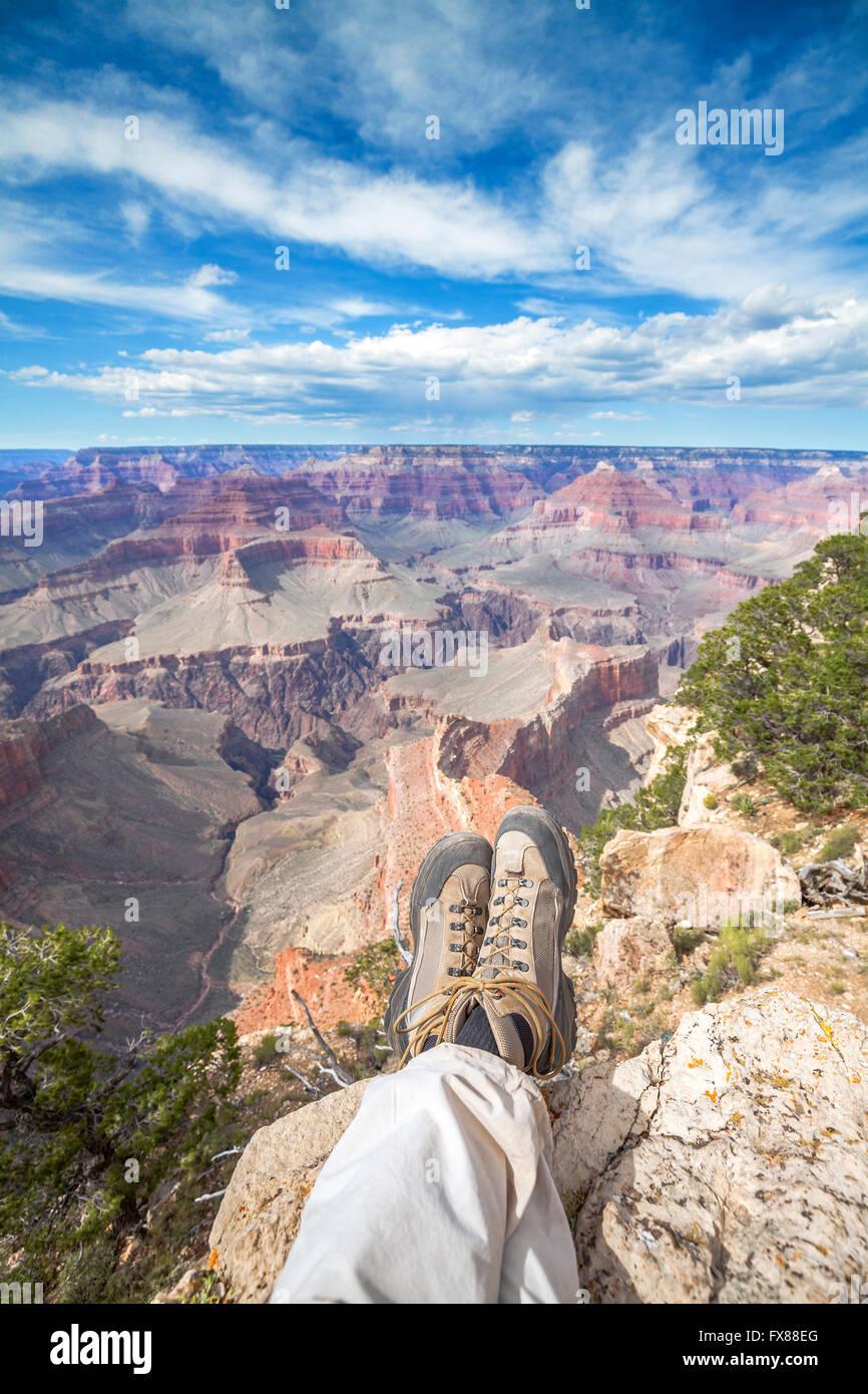 Las piernas de una persona descansando sobre el borde del Gran Cañón, el concepto de unas vacaciones activas. Imagen De Stock