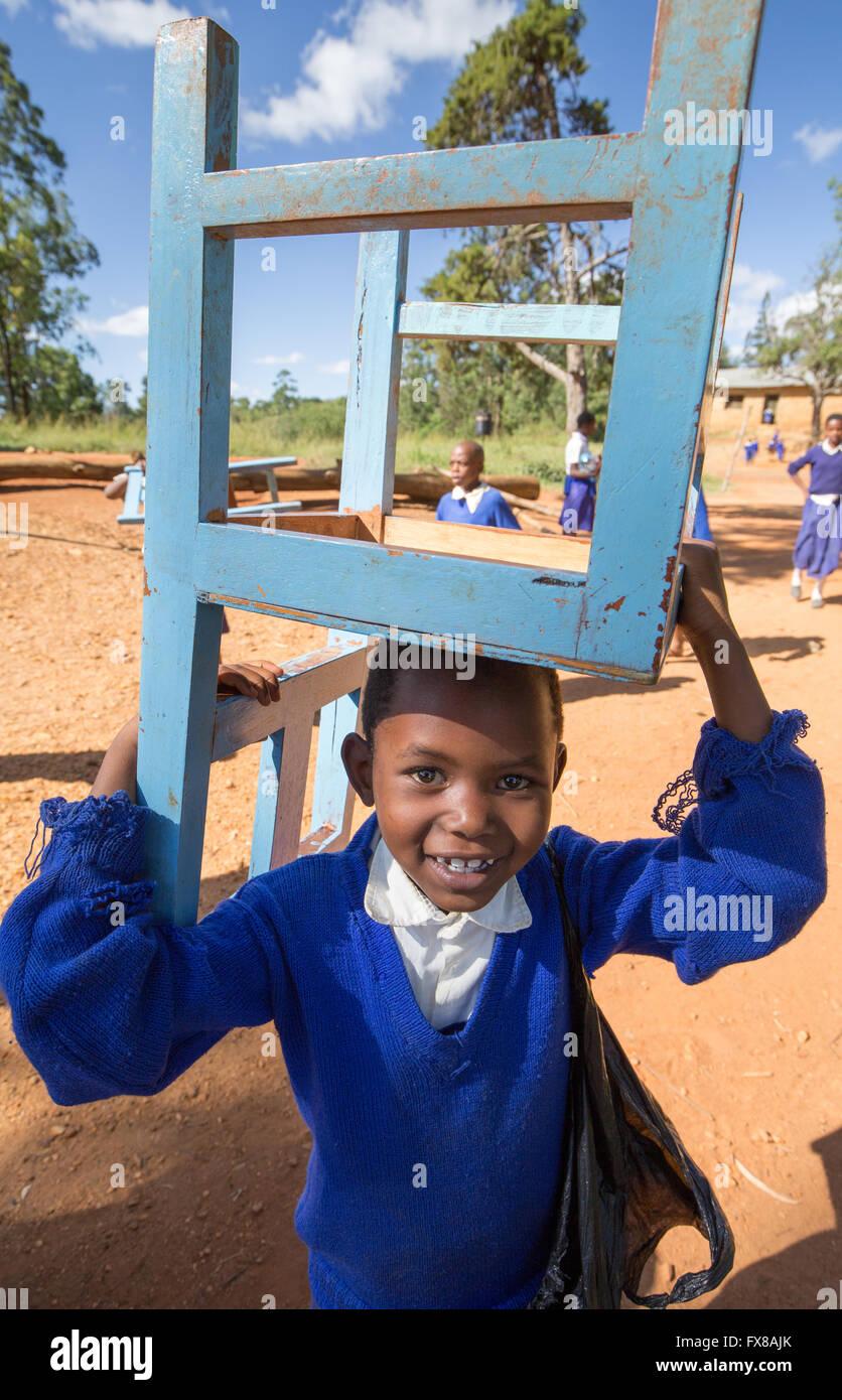 Sonriente colegial de Kenia llevando una silla el regreso a las aulas de una escuela en las colinas del sur de Kenya Imagen De Stock