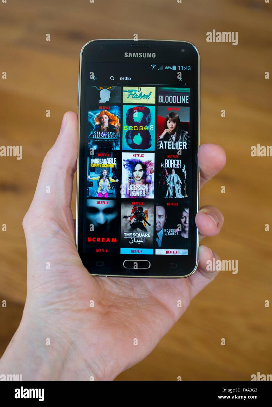 Una mano sujetando un teléfono de Samsung con la app Netlfix original abierto, mostrando el contenido de Netflix. Imagen De Stock