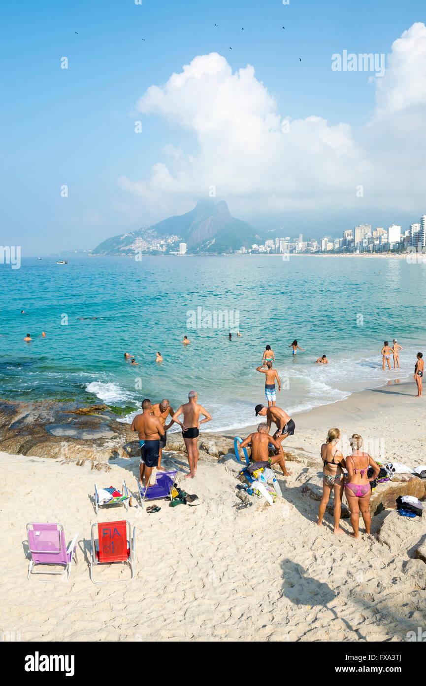 RIO DE JANEIRO - 5 de abril de 2016: Beachgoers tomar el sol en una tranquila mañana en el Arpoador final de Imagen De Stock