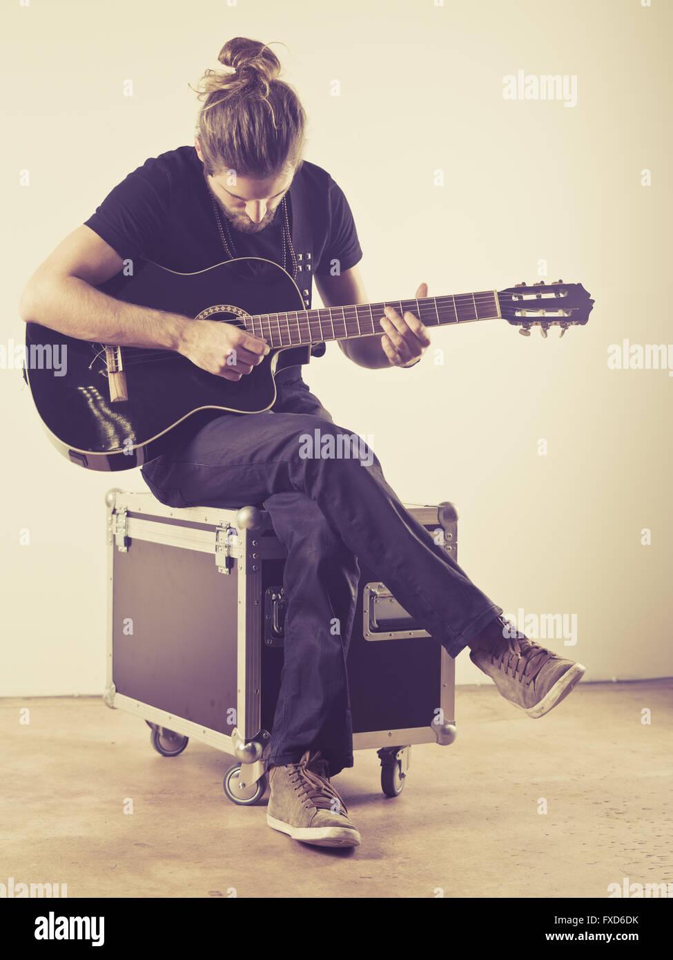 Foto de un joven hombre atractivo con el cabello largo y barba sentado en una maleta y tocando una guitarra acústica. Imagen De Stock