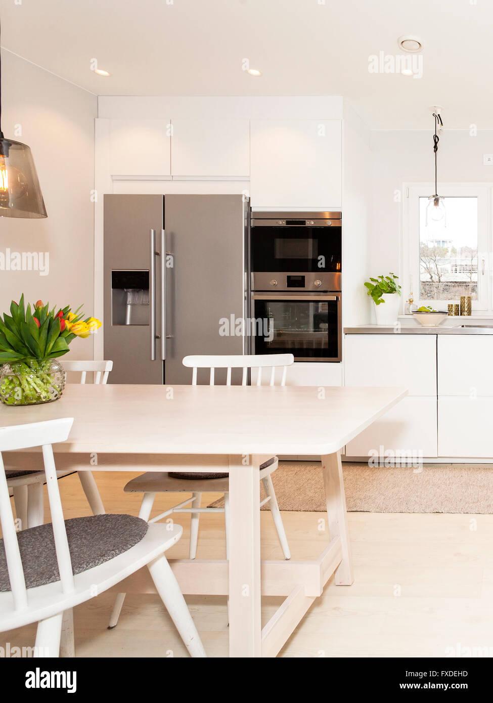 La mesa de la cocina blanca en una elegante cocina con ...