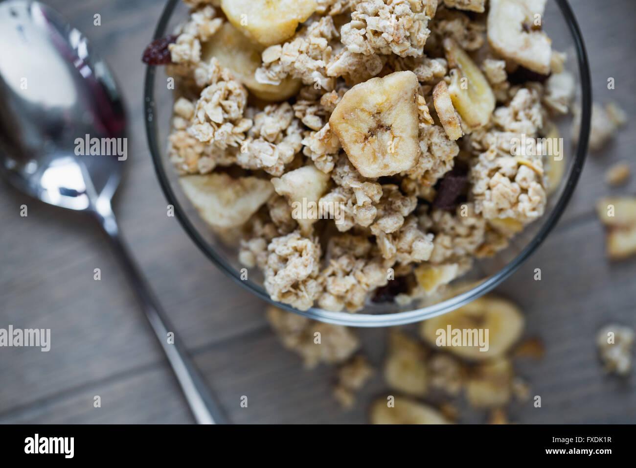 Plato de granola con plátano sobre mesa de madera. Imagen De Stock