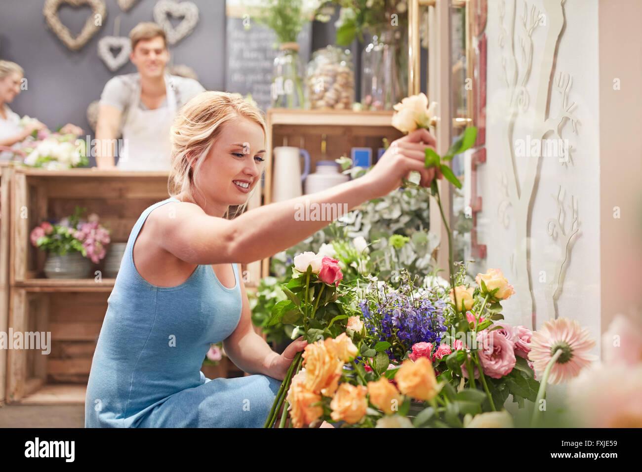 Mujer sonriente recogiendo flores en flower shop Imagen De Stock