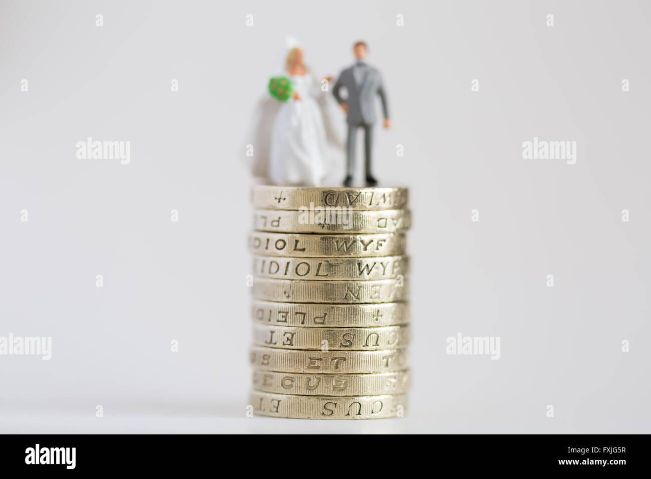 Cerrar/macro fotografía de stock modelo representando el marido y la mujer casada en £1 libras y pila de moneda Foto de stock