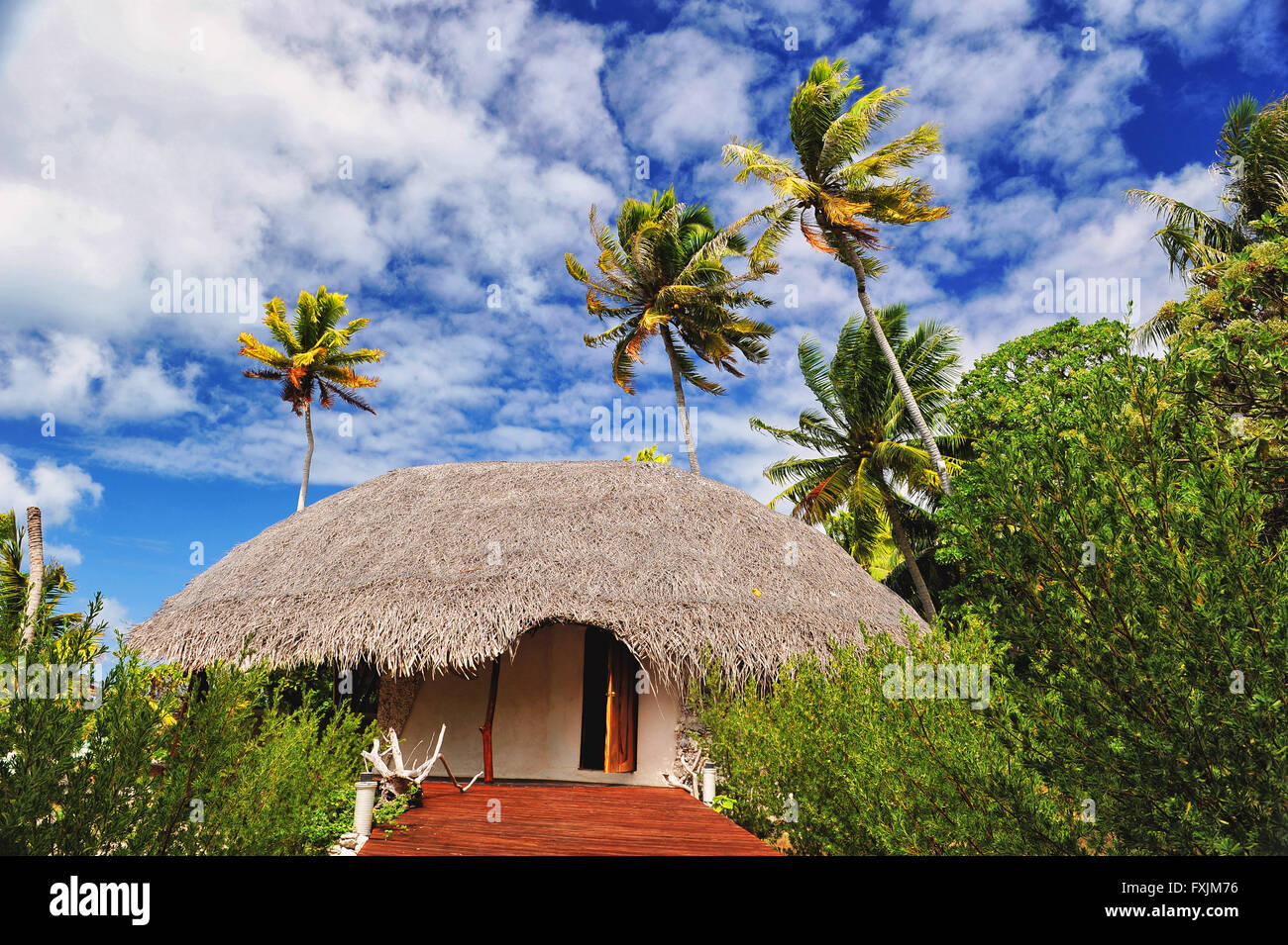 Tikehau, el atolón de las Islas Tuamotu, Polinesia. Un eco resort en medio de palmeras verdes con una bonita postal sky Foto de stock