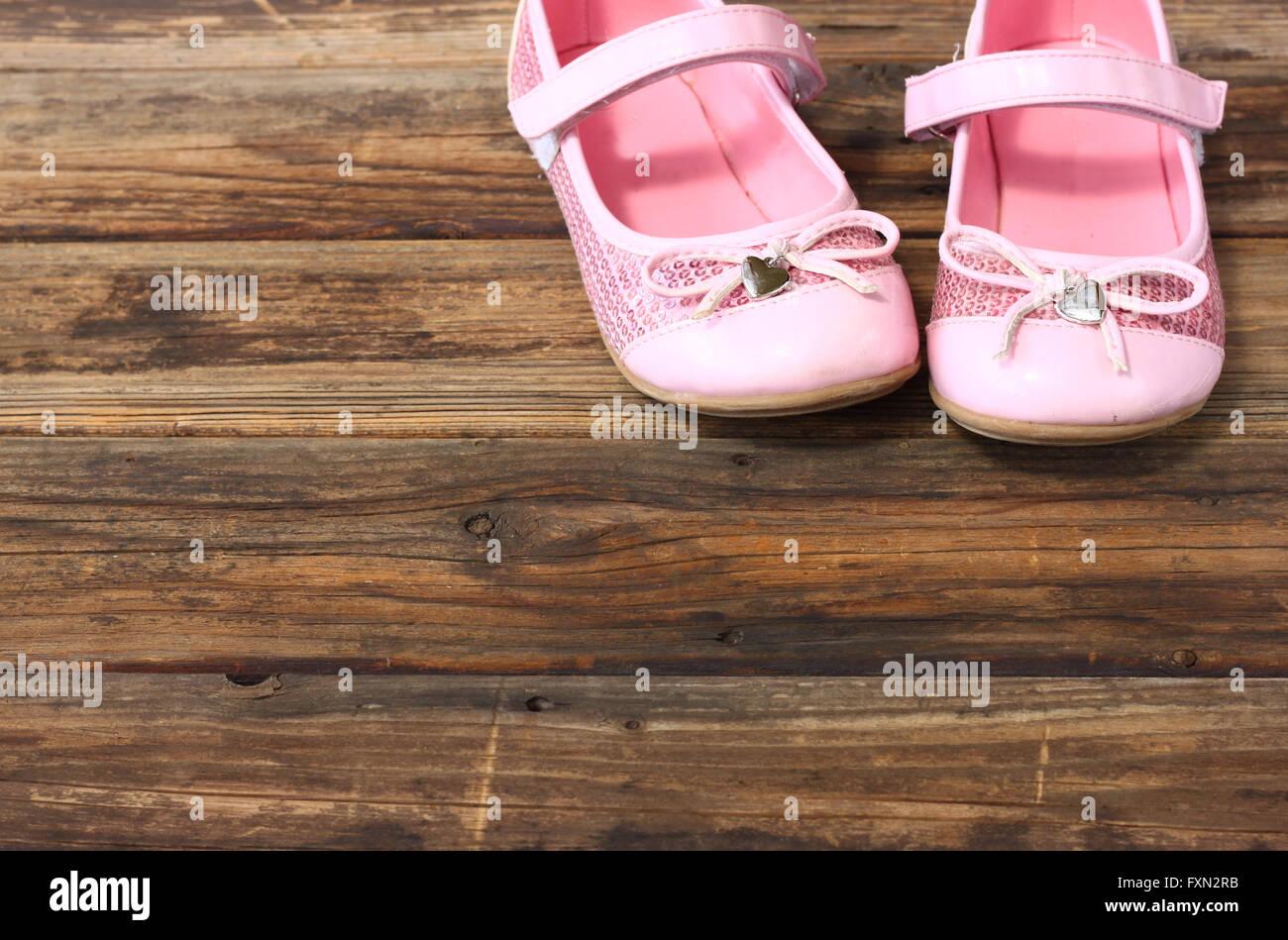 Zapatos niña sobre una plataforma de madera, piso. Imagen De Stock