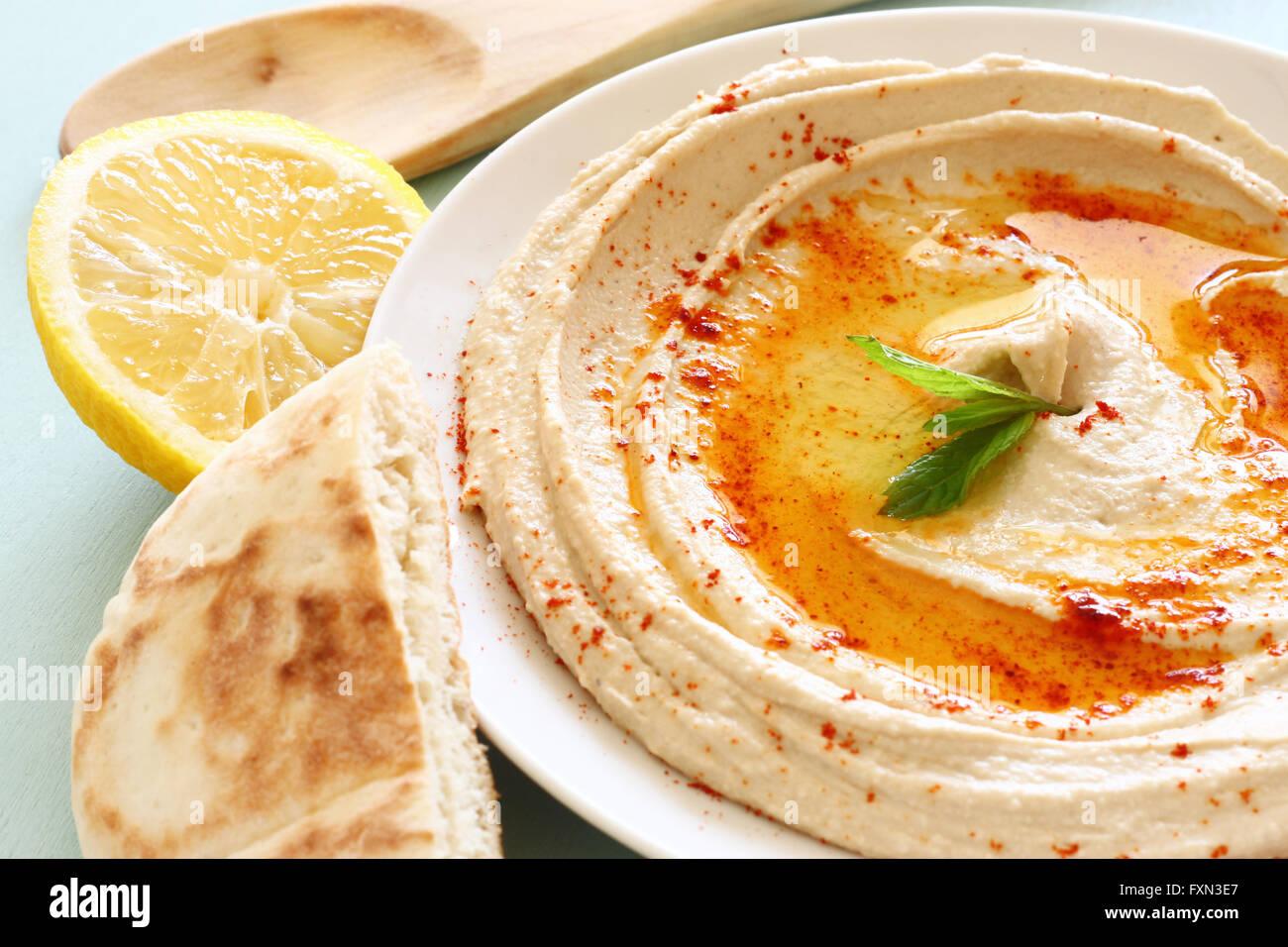 Hummus sumergir la placa en la tabla de madera Imagen De Stock