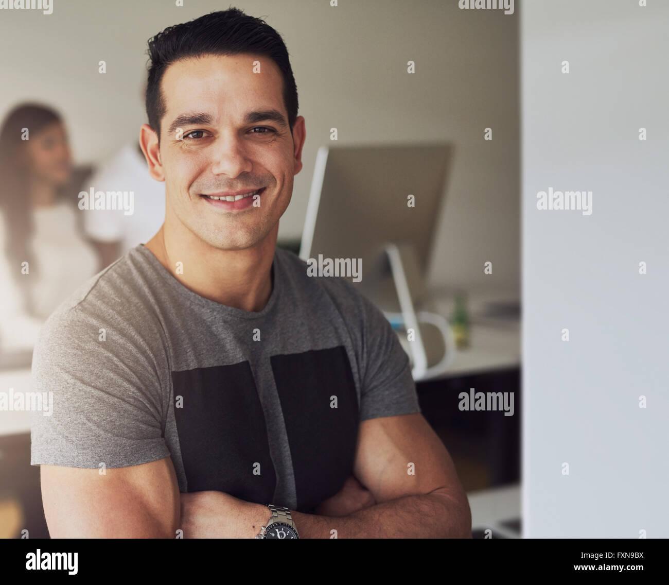 Cierre de seguros hermoso macho trabajador con armas muscular plegada vistiendo la camiseta de manga corta de color Imagen De Stock