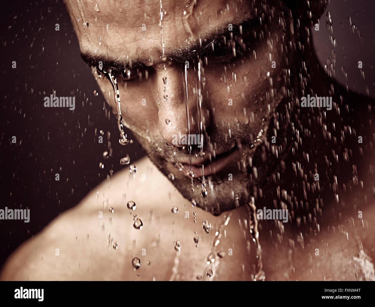 Pensativo hombre atribulado rostro bajo la ducha Foto de stock