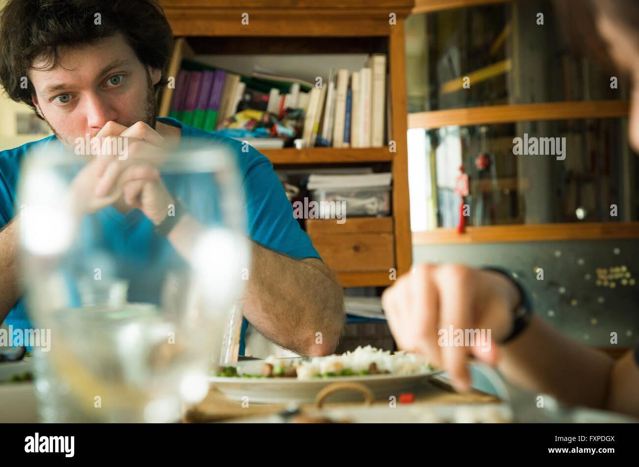 Hombre sentado en la mesa con las manos entrelazadas delante de su boca Imagen De Stock