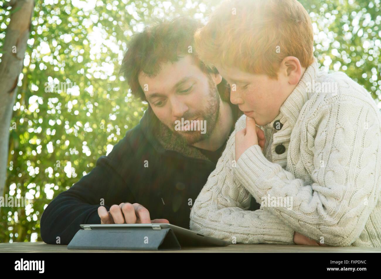 Padre e hijo mirando juntos tableta digital Foto de stock
