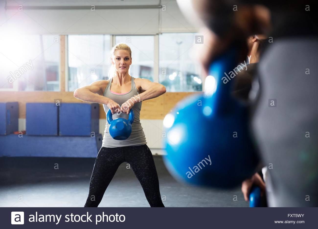 Hombres y mujeres con kettlebells entrenamiento en el gimnasio Imagen De Stock