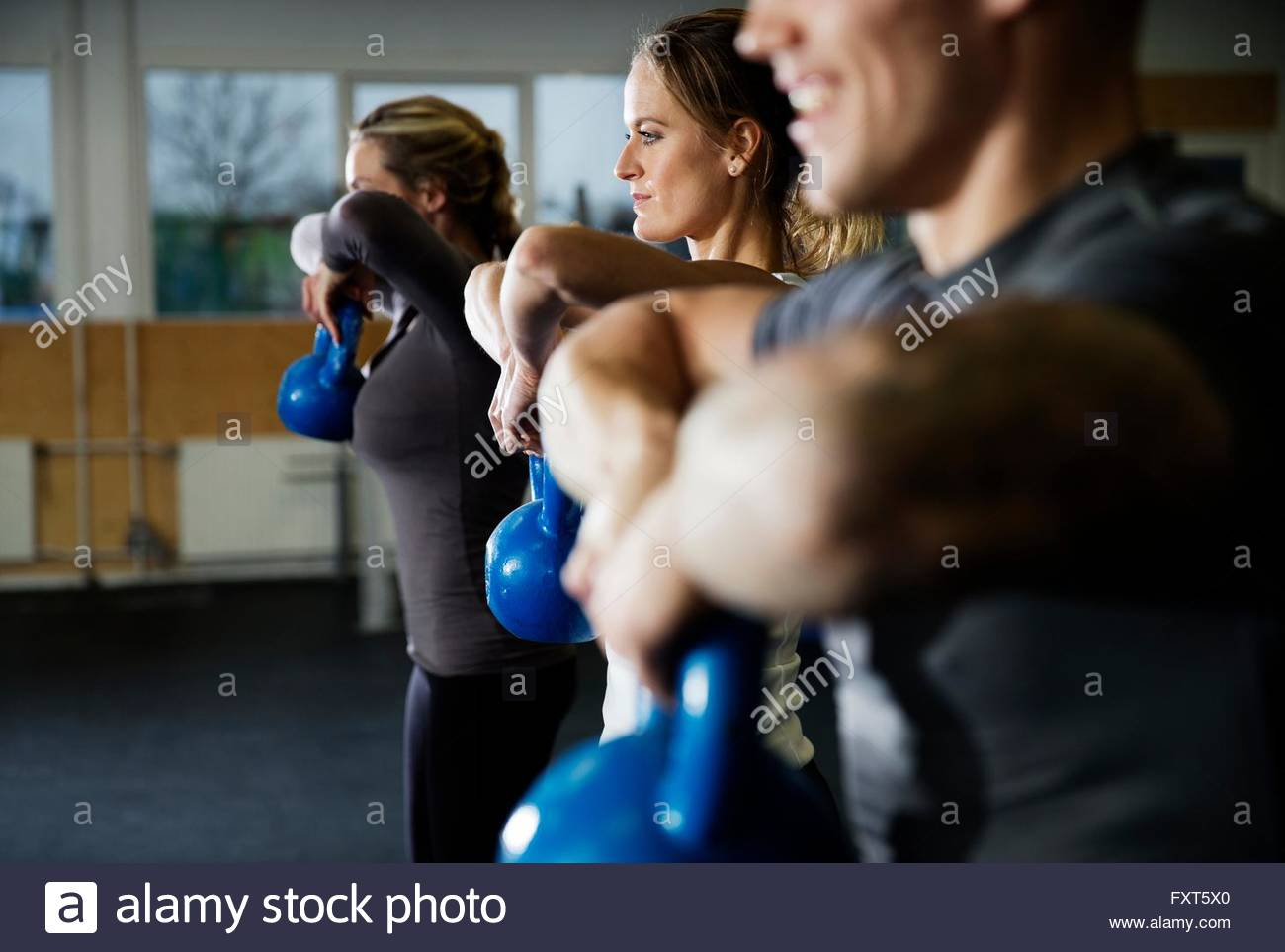 Fila de hombres y mujeres en el gimnasio entrenamiento con kettlebells Imagen De Stock