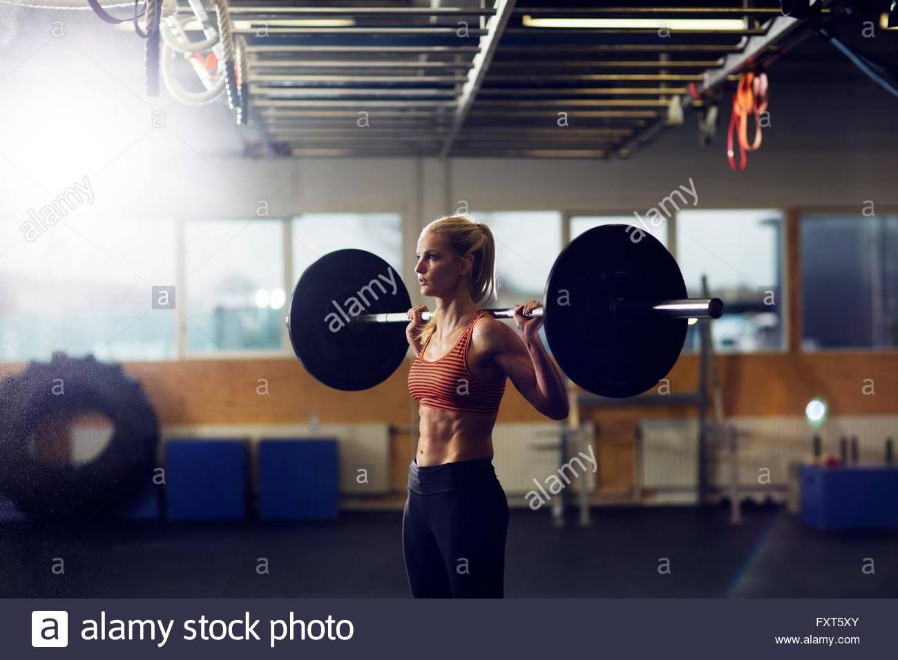 Mujer barbell en hombros de elevación en el gimnasio Imagen De Stock