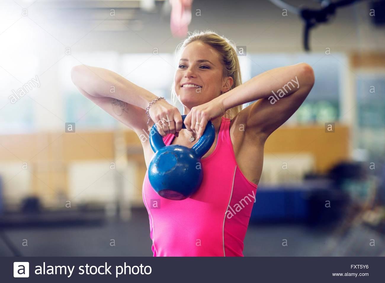 Mujer joven levantamiento kettlebell en gimnasio Imagen De Stock