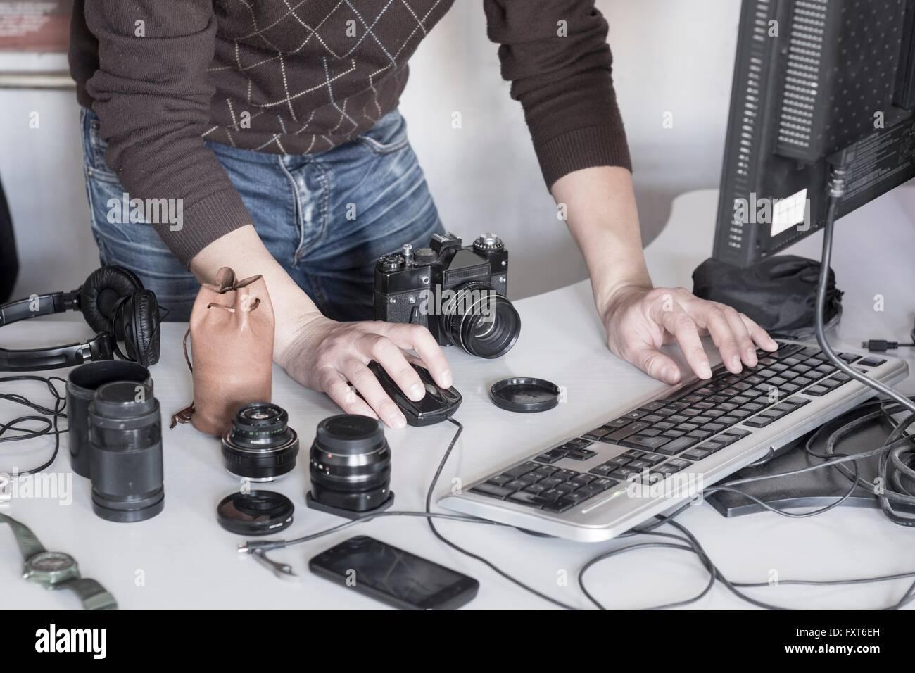 Fotógrafo cargar fotos desde la cámara al ordenador en studio Foto de stock