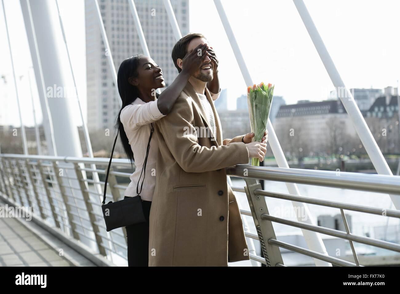 Hombre de pie en el puente, sosteniendo flores, mujer sorprendente él, cubre los ojos desde atrás Imagen De Stock