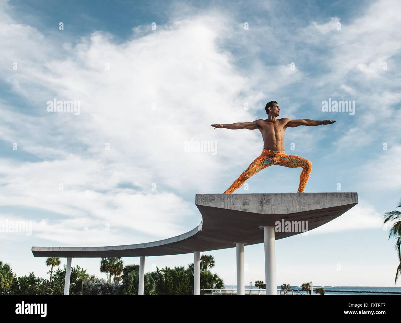 Hombre maduro equilibrio sobre la estructura, el parque South Pointe, South Beach, Miami, Florida, USA. Imagen De Stock