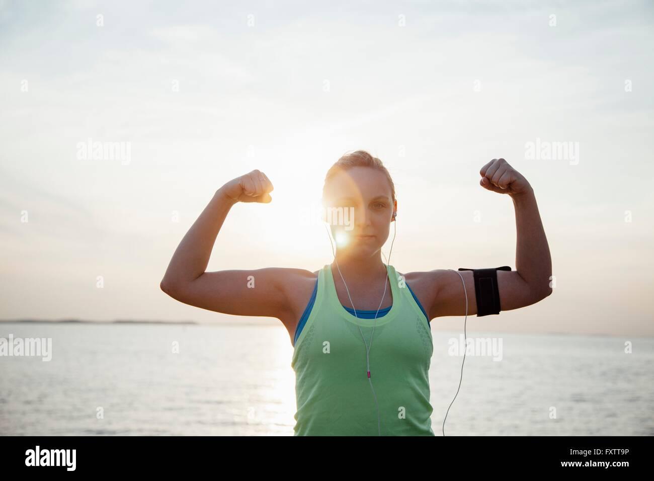 Mujer vistiendo rastreador, flexionando los músculos de los brazos levantados mirando a la cámara Imagen De Stock