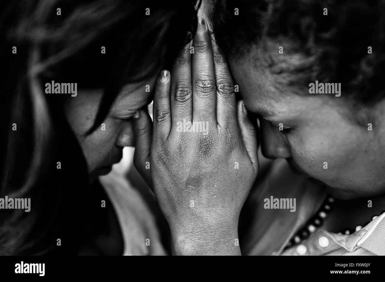 Las mujeres colombianas, con las manos juntas, orar durante la ceremonia religiosa realizada en una casa de la iglesia Imagen De Stock