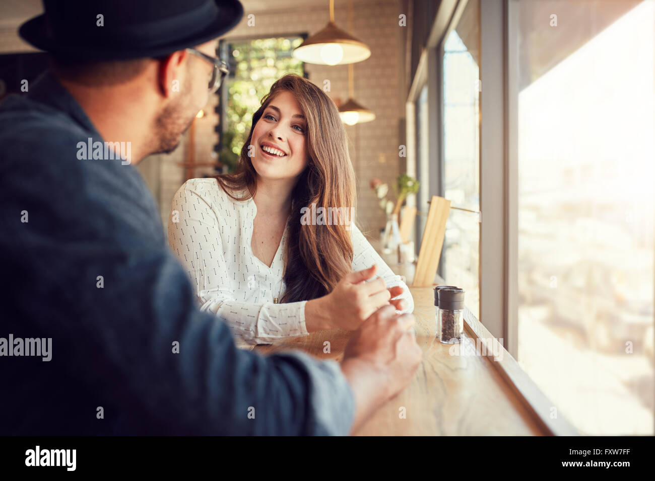 Mujer sonriente sentado en un café y hablar con su novio. Pareja joven pasar tiempo en la cafetería. Imagen De Stock