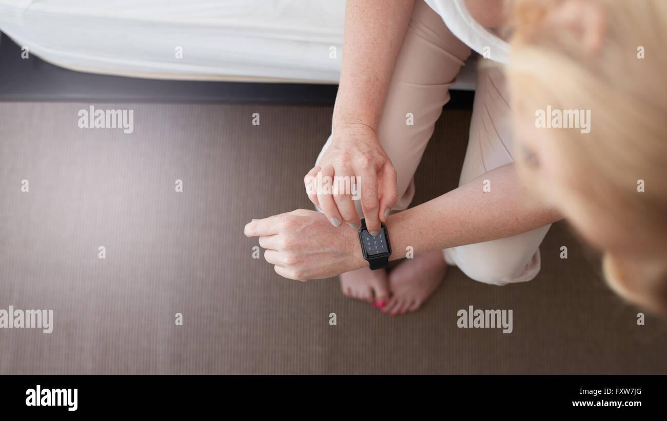 Vista superior de la foto de una mujer que utiliza Smart Watch. Ella está marcando un número de teléfono Imagen De Stock