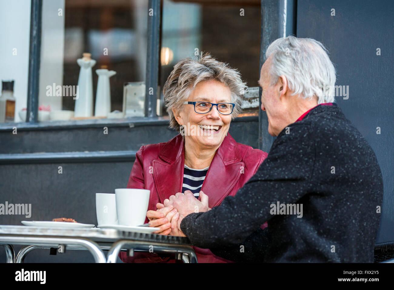 Romántica pareja senior manos al café en la acera Imagen De Stock