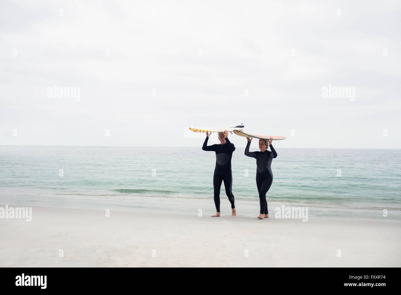 Las parejas ancianas en llevar traje de neopreno, tablas de surf sobre la cabeza Foto de stock