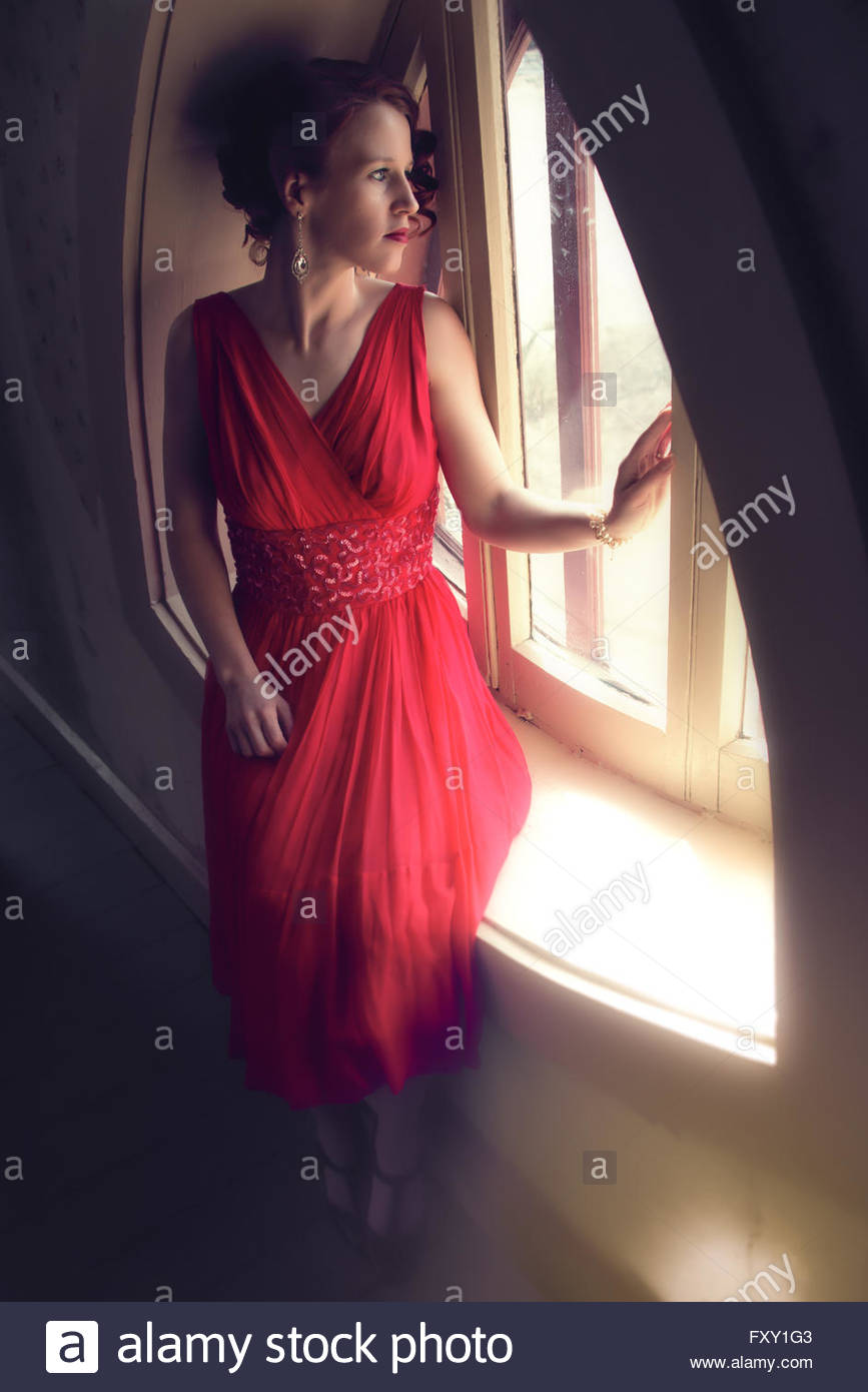 Mujer en 1940 vestido de noche sentada por la ventana Imagen De Stock