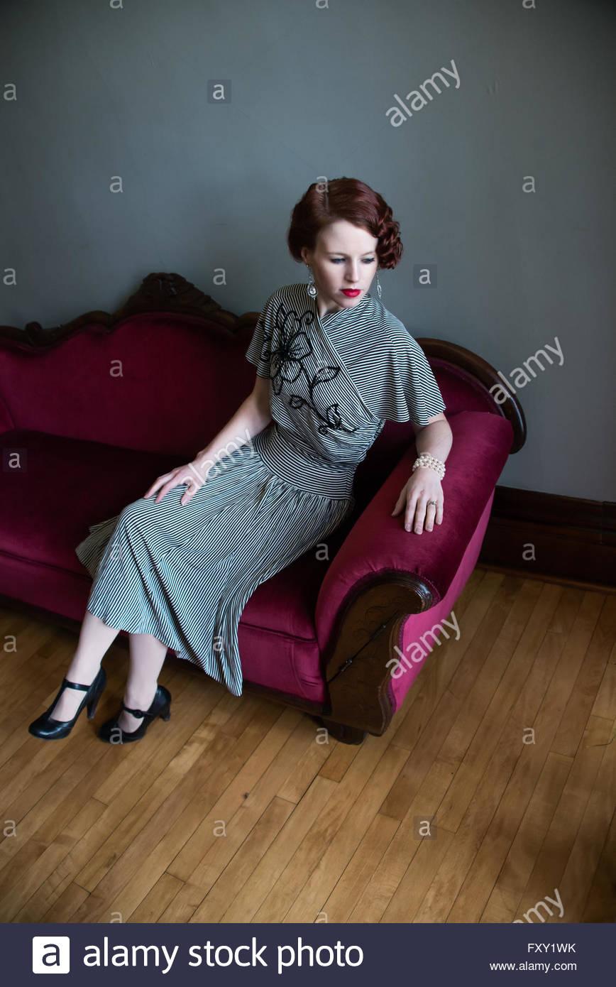 Mujer en el Vintage 1940 vestido sentado en el sofá Imagen De Stock