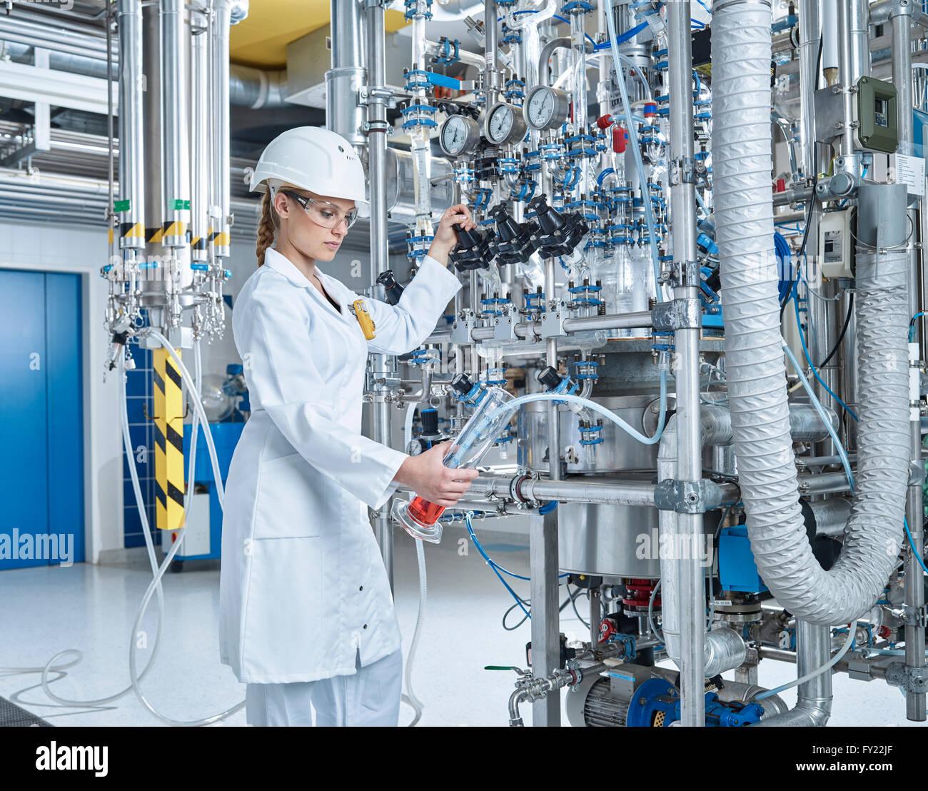 Hembra, ayudante del laboratorio químico de 20-25 años, llenar un vaso con un líquido rojo en un Imagen De Stock