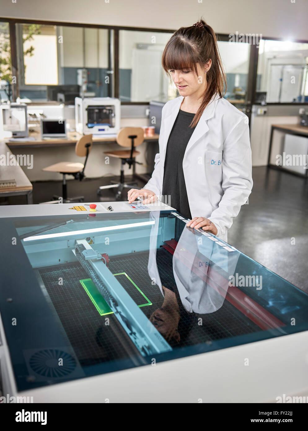 Técnico femenino, de 20-25 años, con una bata blanca de laboratorio, usando un cortador láser en Imagen De Stock