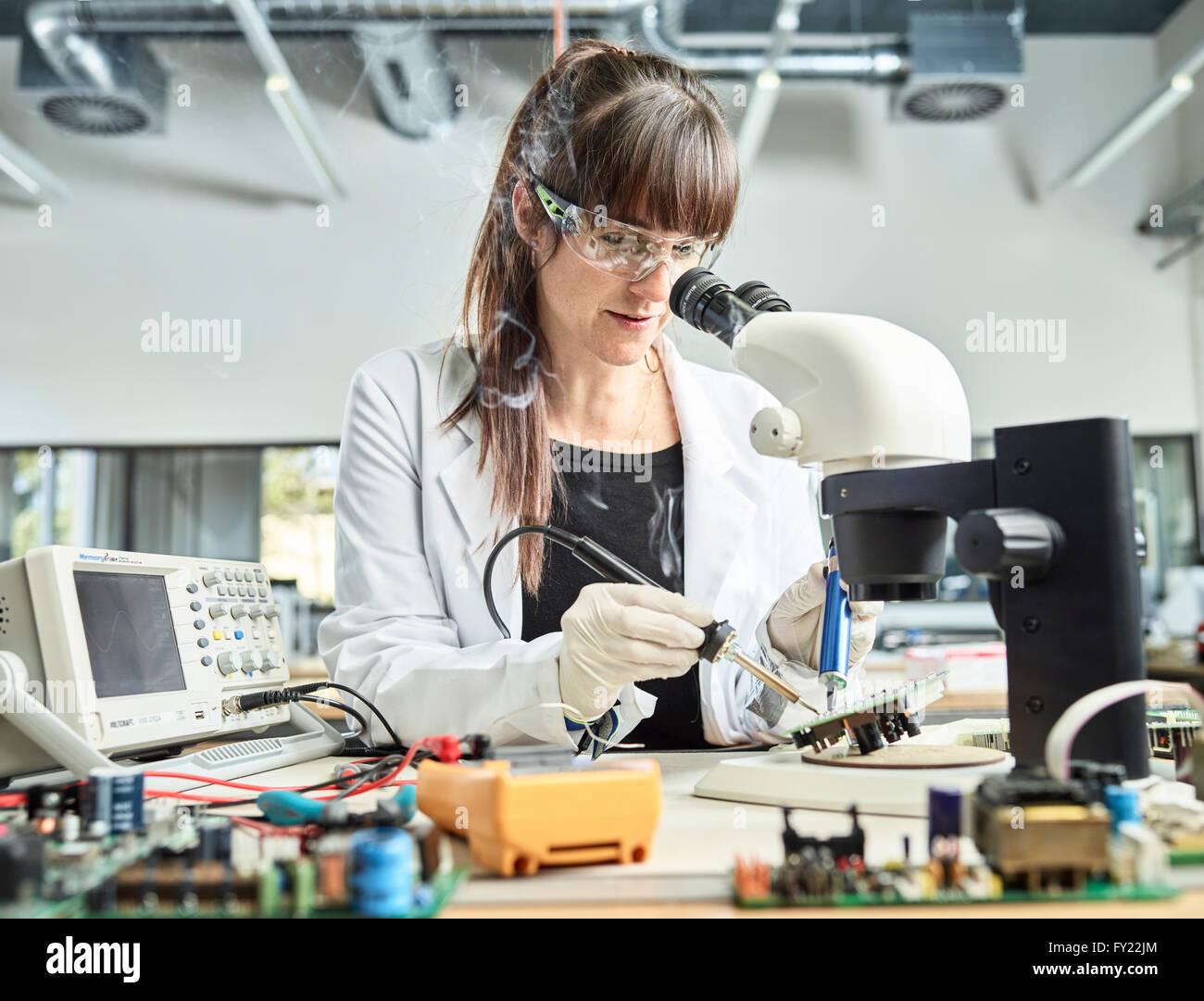 Técnico femenino, de 20-25 años, con una bata blanca de laboratorio, soldadura de una placa de circuito Imagen De Stock