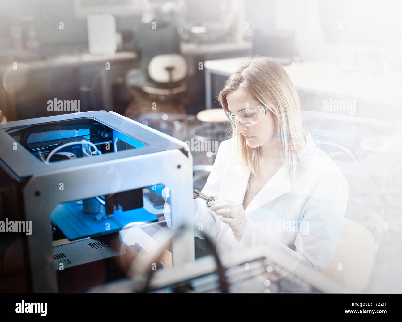 Técnico hembra, 25-30 años, en bata blanca de laboratorio y gafas, el control del proceso de impresión Imagen De Stock